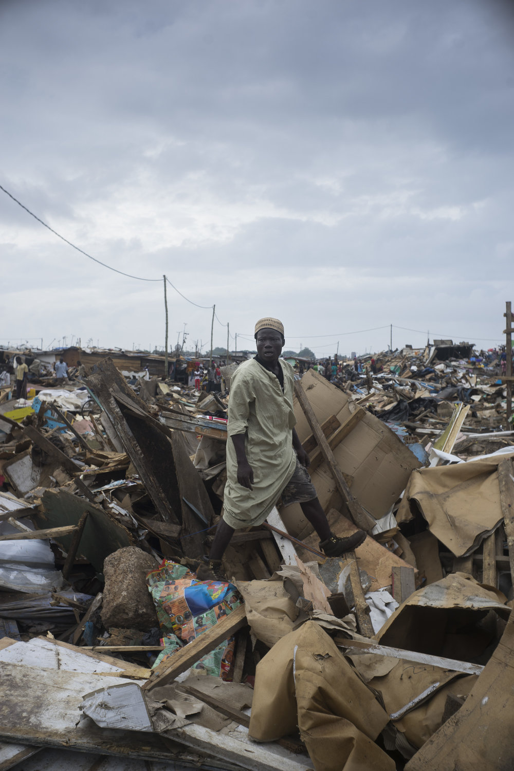 Awal stands atop his freshly demolished home. He built his home by hand three years ago.