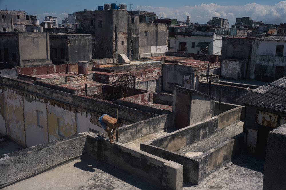 Arian, a seventeen-year-old Cuban, runs across the roof of his building complex. He lives in Central Havana, Cuba.