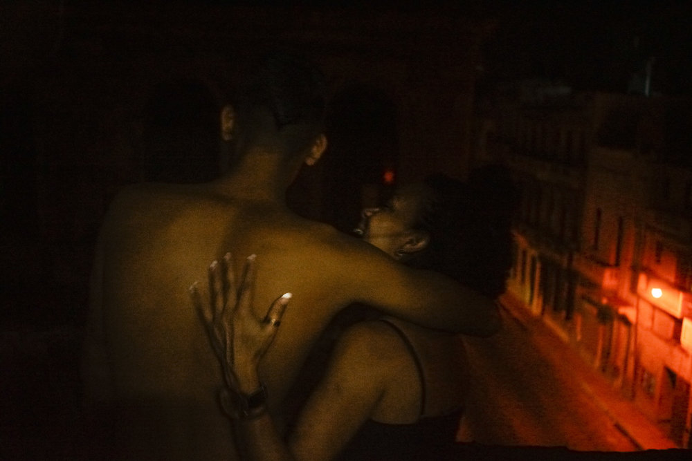 Arian and Nidieska embrace on the balcony outside of their room.