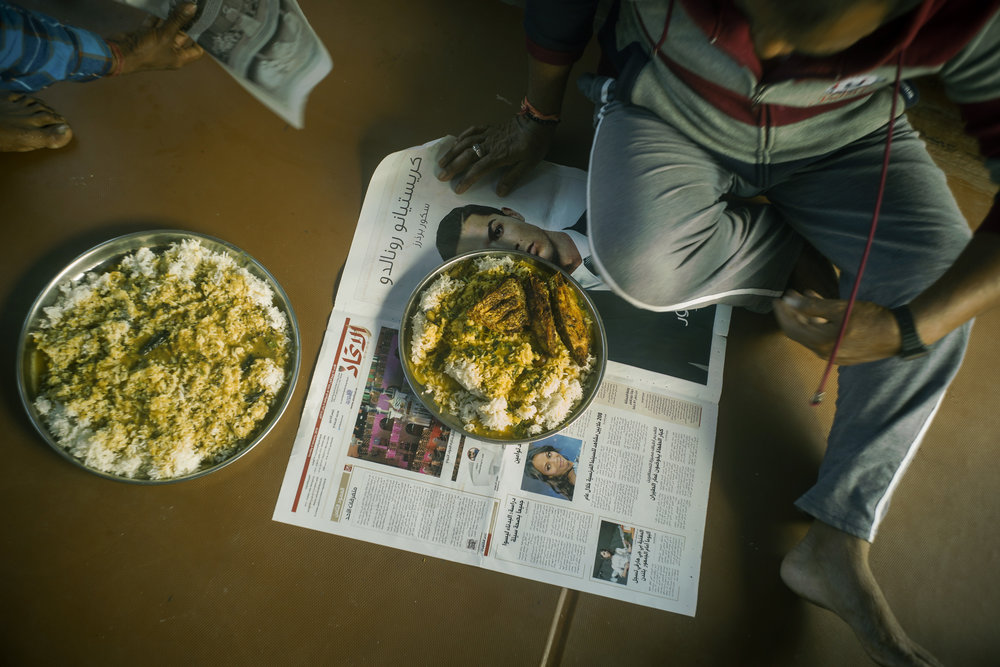 Denish and his father, Eddy Krishna, sit down for a meal of freshly caught fish and rice.