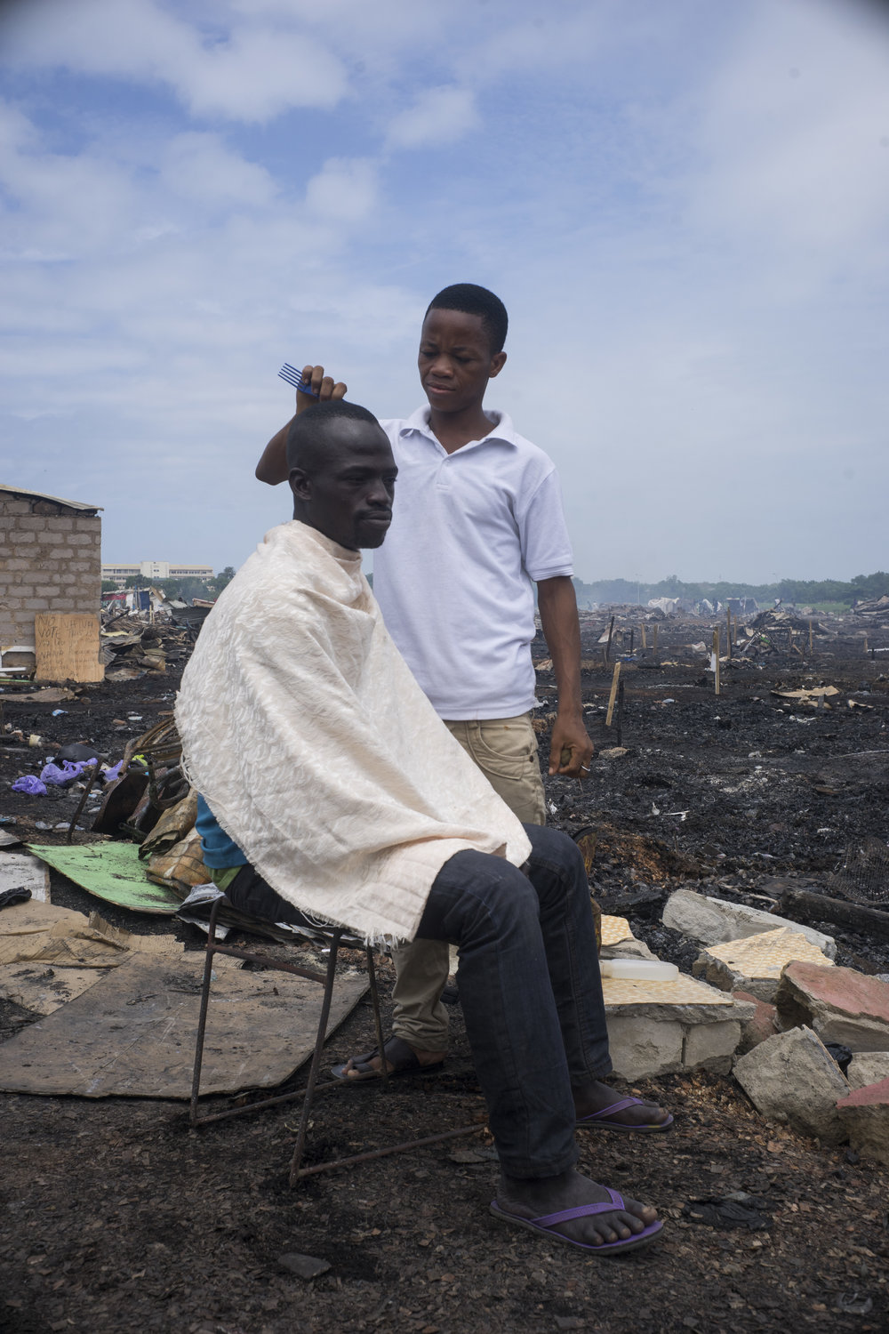 Justice, 37, sits down for a haircut. Business and rebuilding resume only a few days after the demolition.