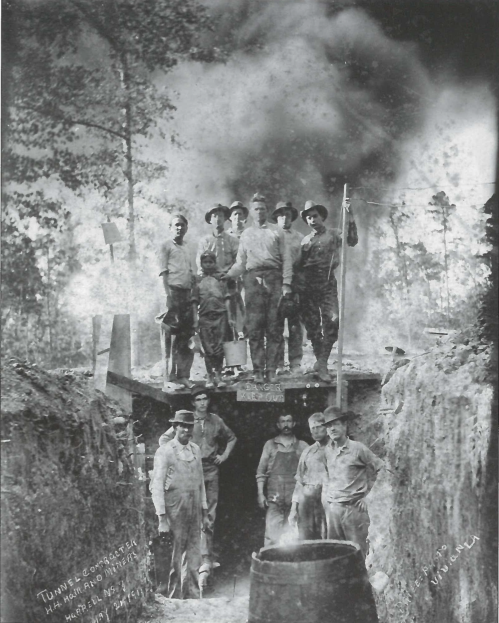 Workers—including a young boy—pose around the tunnel that a former coal miner dug to relieve the oil well fire at Harrell's No. 7 in Vivian, 1911