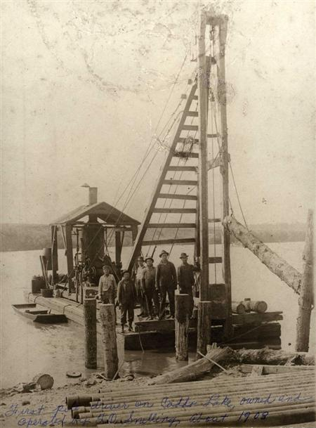 The improvised crane workers used to construct oil derricks atop of Caddo Lake, 1908