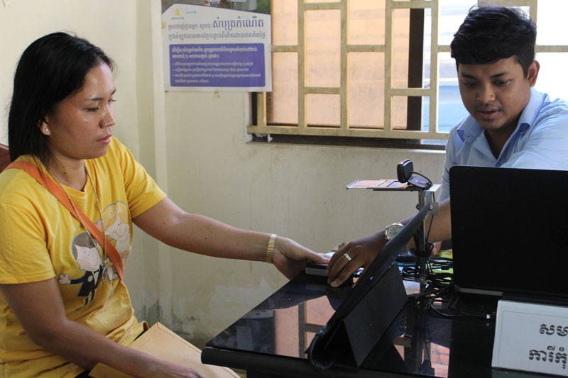 A woman gets her fingerprint scanned at a pilot election registration centre in Phnom Penh.  Image Source.