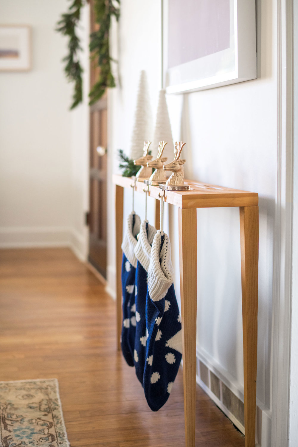 These blue knit stockings coordinated with the deeper blue ornaments on the tree. Things like buying an extra stocking are making things feeling very real that we are going to be a family of three soon. I love that these gold reindeer stocking hooks can look more modern or more traditional depending on the setting.
