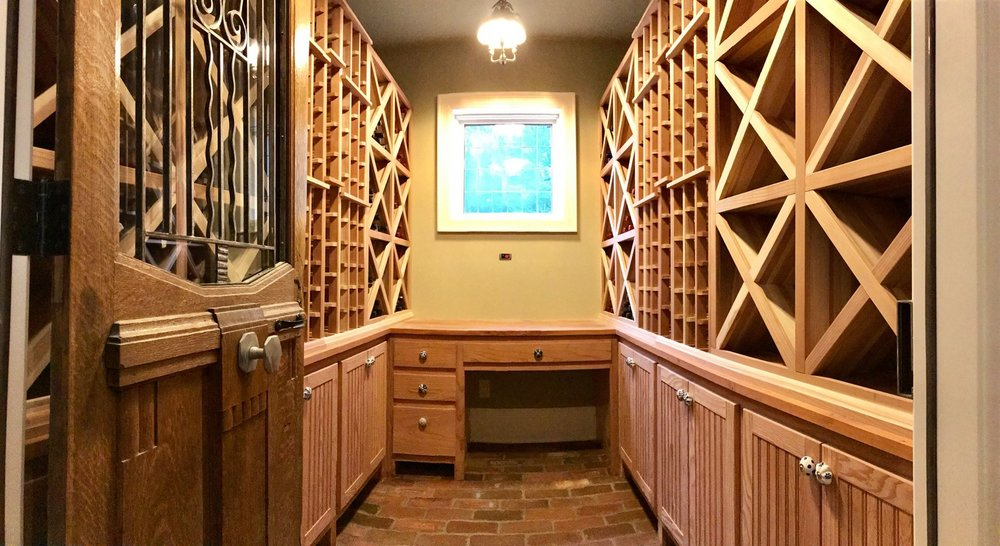 The racking and cabinets in this custom wine cellar are made from western redwood. Countertops are Spanish mahogany and the floor is made from brick that was reclaimed from a horse stable on the property.