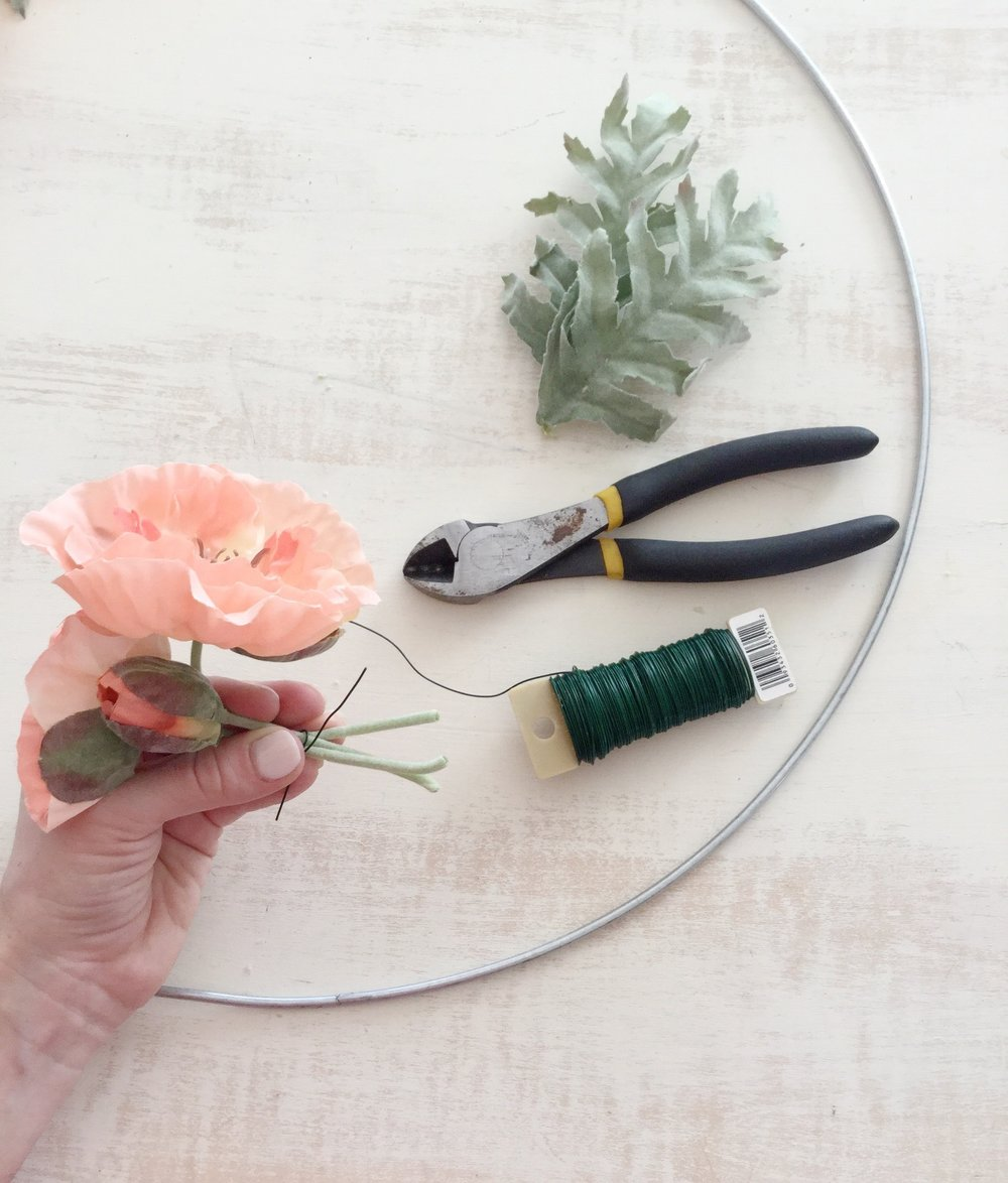 Step 2: Create bouquet - Next, gather your flowers and wrap a piece of floral wire around them, creating a miniature bouquet. *Tip: once you have your flowers together, if you twist the wire around itself and then wrap it back around the flower stems, this should keep everything nice and secure.
