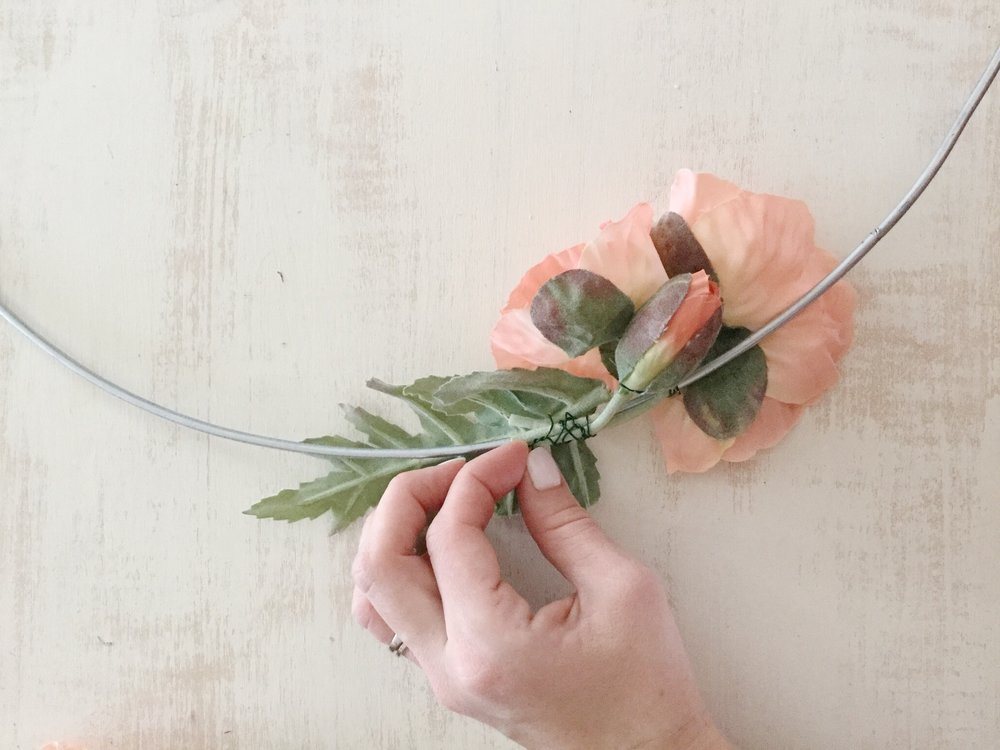 Step 5: Attach leaves - Next, secure the floral wire that you attached to the leaves around the floral hoop.