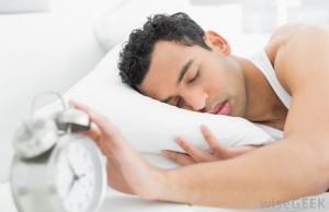 man-asleep-on-pillow-with-hand-on-alarm-clock