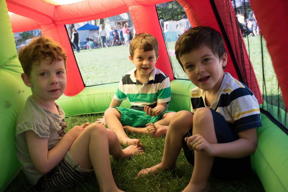 Three smiling kiddos sitting in a bouncehouse at Littles
