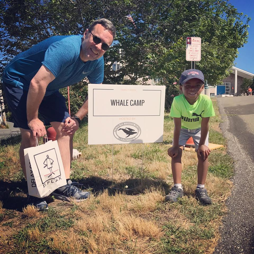 A grownup and a kiddo smiling with the whale camp sign