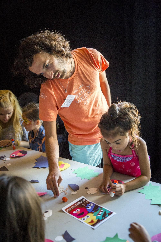 A family week intern helping at art camp