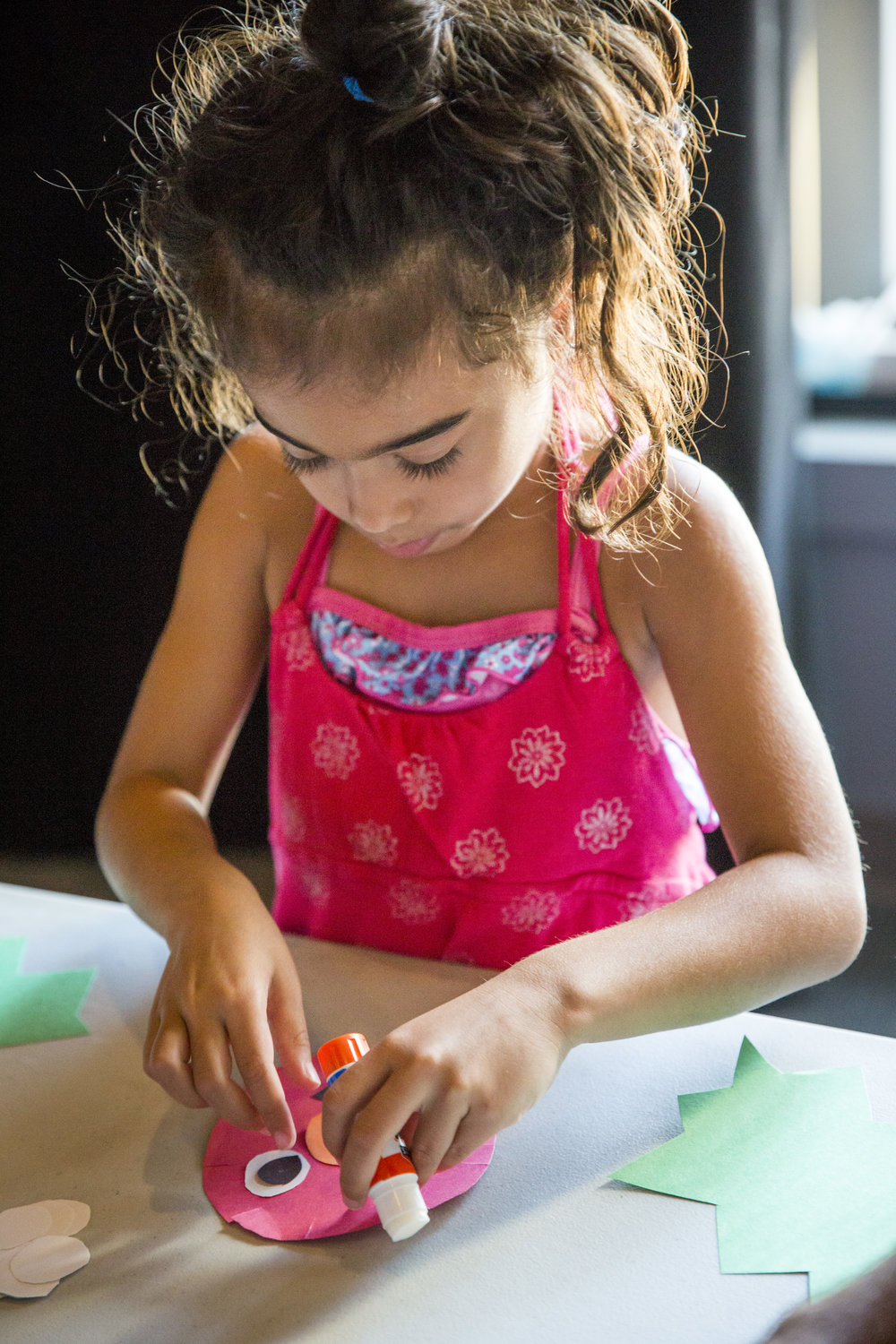A young kiddo in pink using a glue stick to make some art