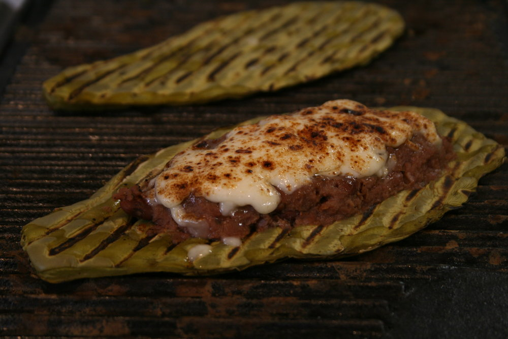 Nopalitos topped with Refried Beans and Queso Oaxaca,  photo my Adriana Almazan Lahl from  Celebraciones Mexicanas: History, Traditions and Recipes  ALL RIGHTS RESERVED