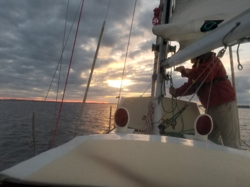 Shortly after leaving Elizabeth City before dawn, Dobbs hoists the mainsail.