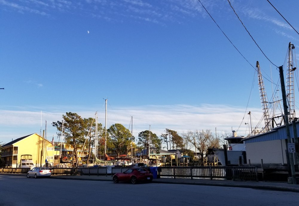 The town dock is visible to the left of the parked red car.