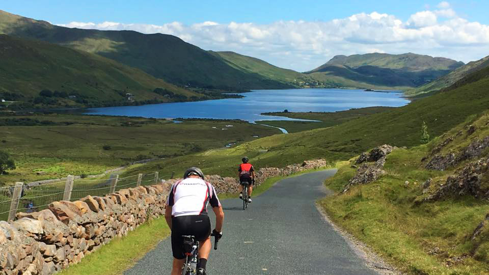 Cyclists on challenge tour with Irish Mountains and Lake in background.