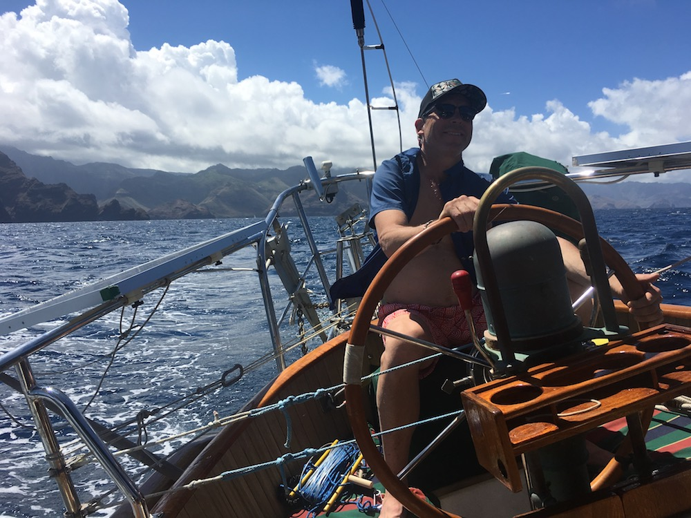 Dad steering Sedna off of Nuku Hiva at the start of our 4-day passage to the Tuamotus.