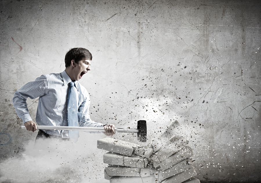 Young angry businessman crashing bricks with hammer