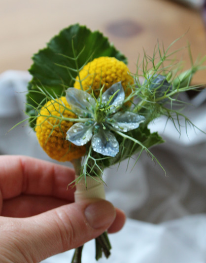 groom boutonniere of yellow craspedia and blue nigella
