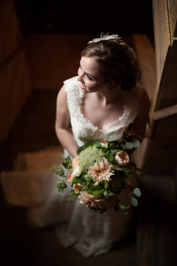 bride with wedding flowers at cottonwood barn