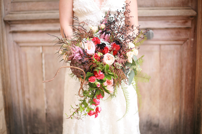rustic floral bouquet with pink, peach and red flowers and textured foliage