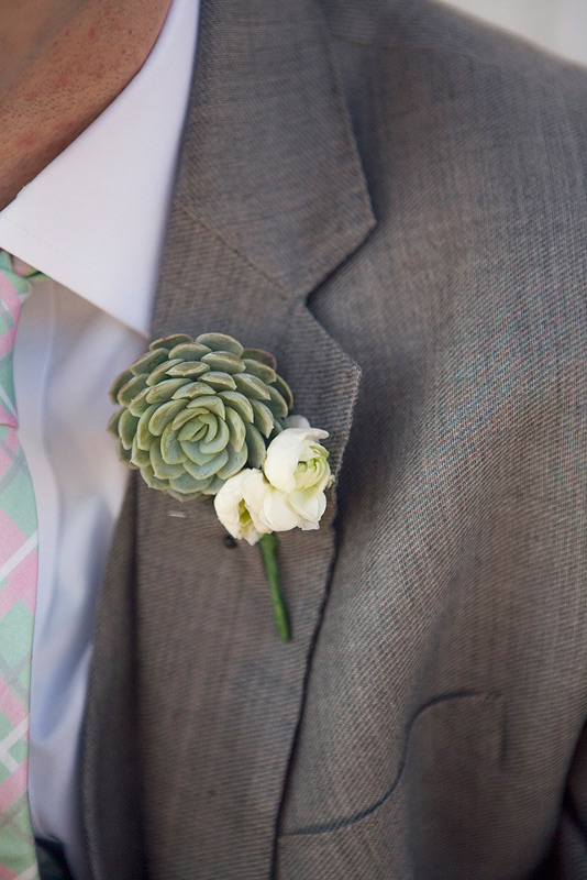 groom boutonniere of white ranunculus and succulent
