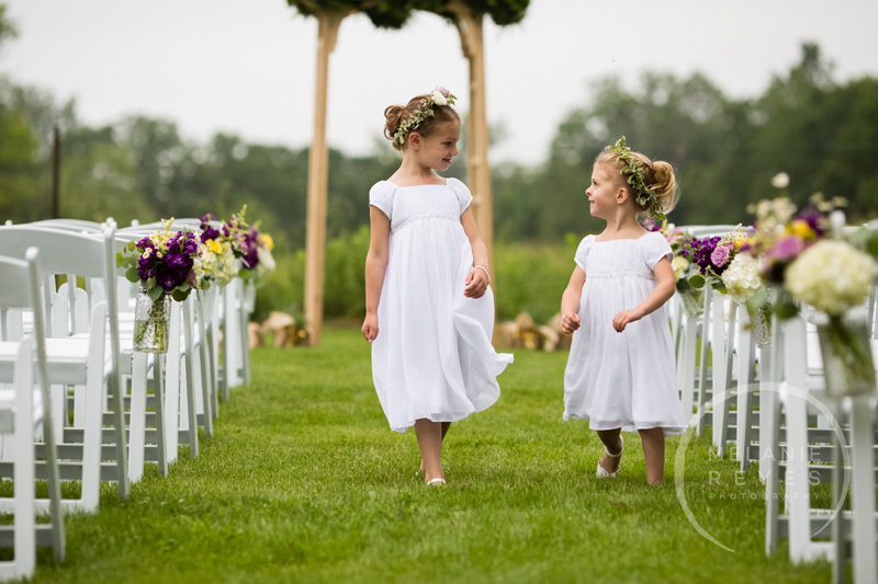 flower girls down the aisle outdoor barn wedding