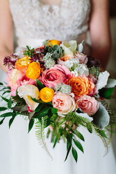 spring wedding bouquet in peach, blush, yellow, orange and pink