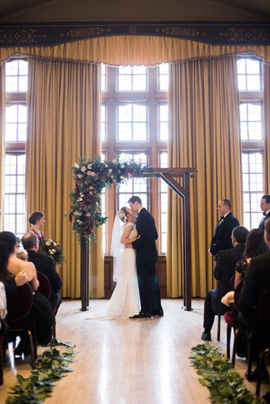wedding ceremony under floral arch at michigan league ballroom