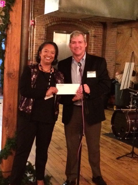 Operation Fuel Acting Director Brenda Watson accepts check from GoodWorks Insurance President Paul Brian.