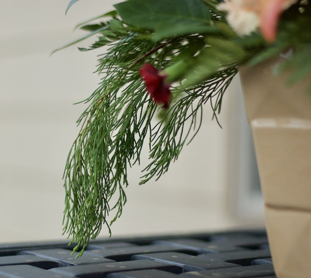 Seasonal greenery draping over an appropriately colored vase