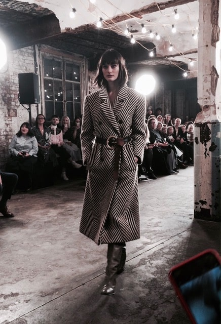 A belted herringbone trench coat worn with long boots. Picture: Bel Jacobs.