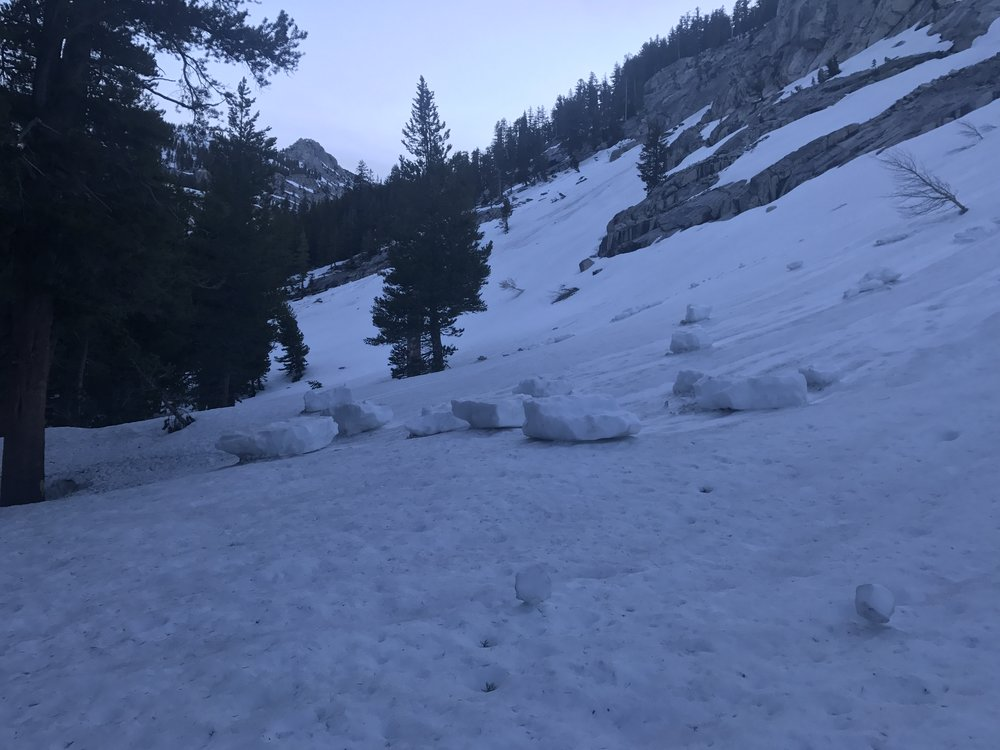 Big snow blocks at the end of a small avalanche slide.