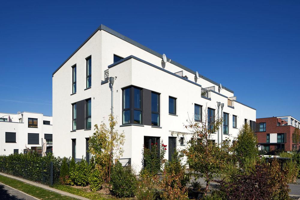 Weisses Mehrfamilienhaus mit schönem Vorgarten
