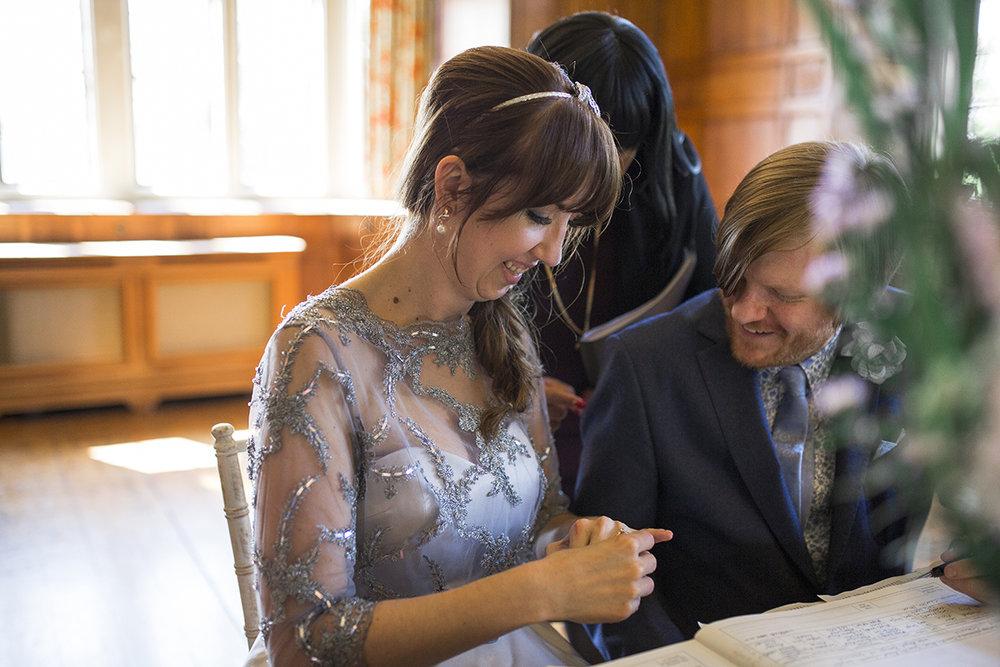 Bride looking at wedding ring Sophie Lake Photography