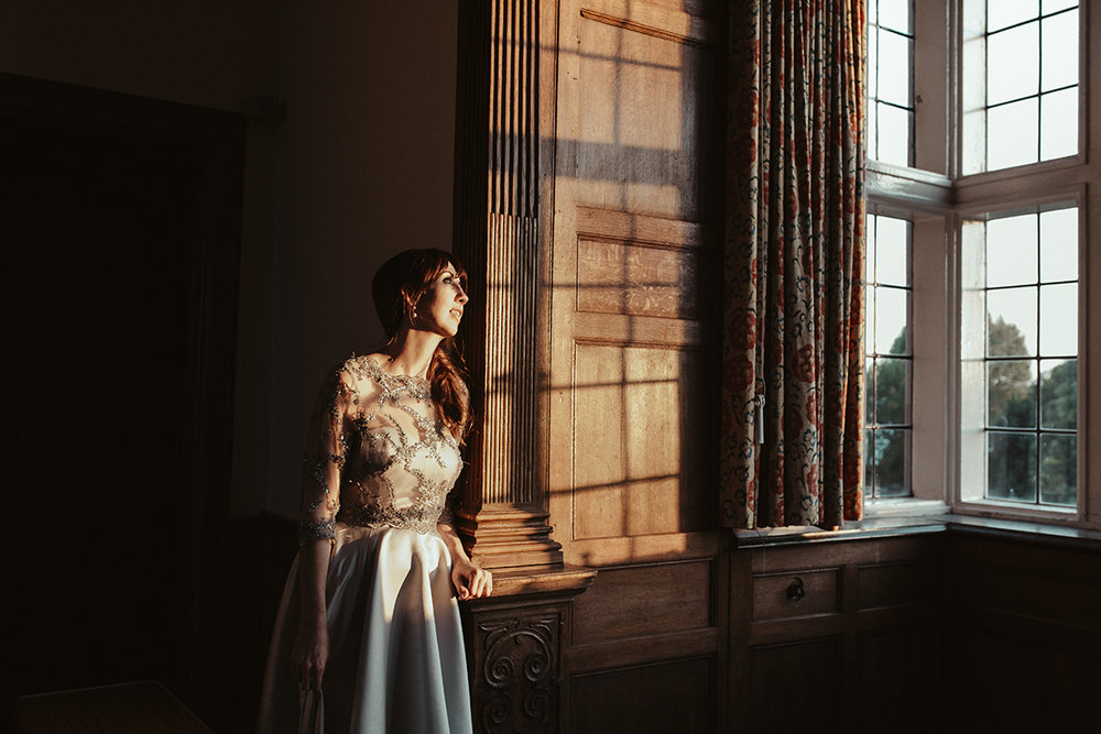 Bride standing in window light Sophie Lake Photography