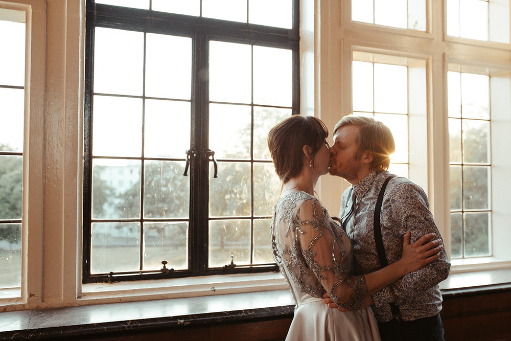 Bride and Groom kissing by window Sophie Lake Photography