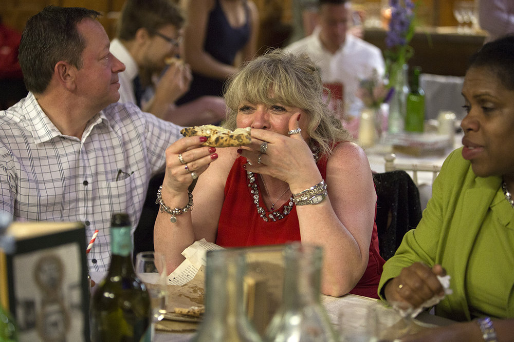 Wedding guest eating pizza Sophie Lake Photography