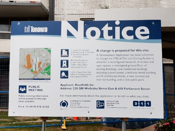 A development notice board stands outside 650 Parliament Street, fenced off since a basement electrical fire on August 21st caused extensive smoke damage to the two towers.  Photo: Jahan A., Jamhoor