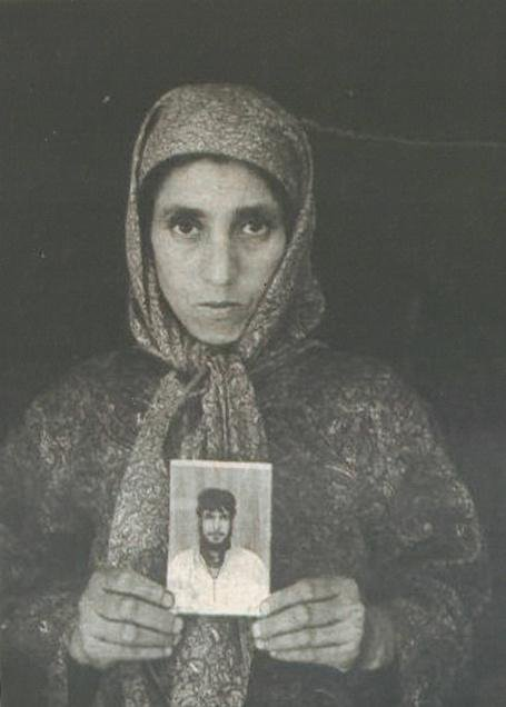 A woman holding a photograph of her relative disappeared by the Indian forces. Photo:    APDP Archives