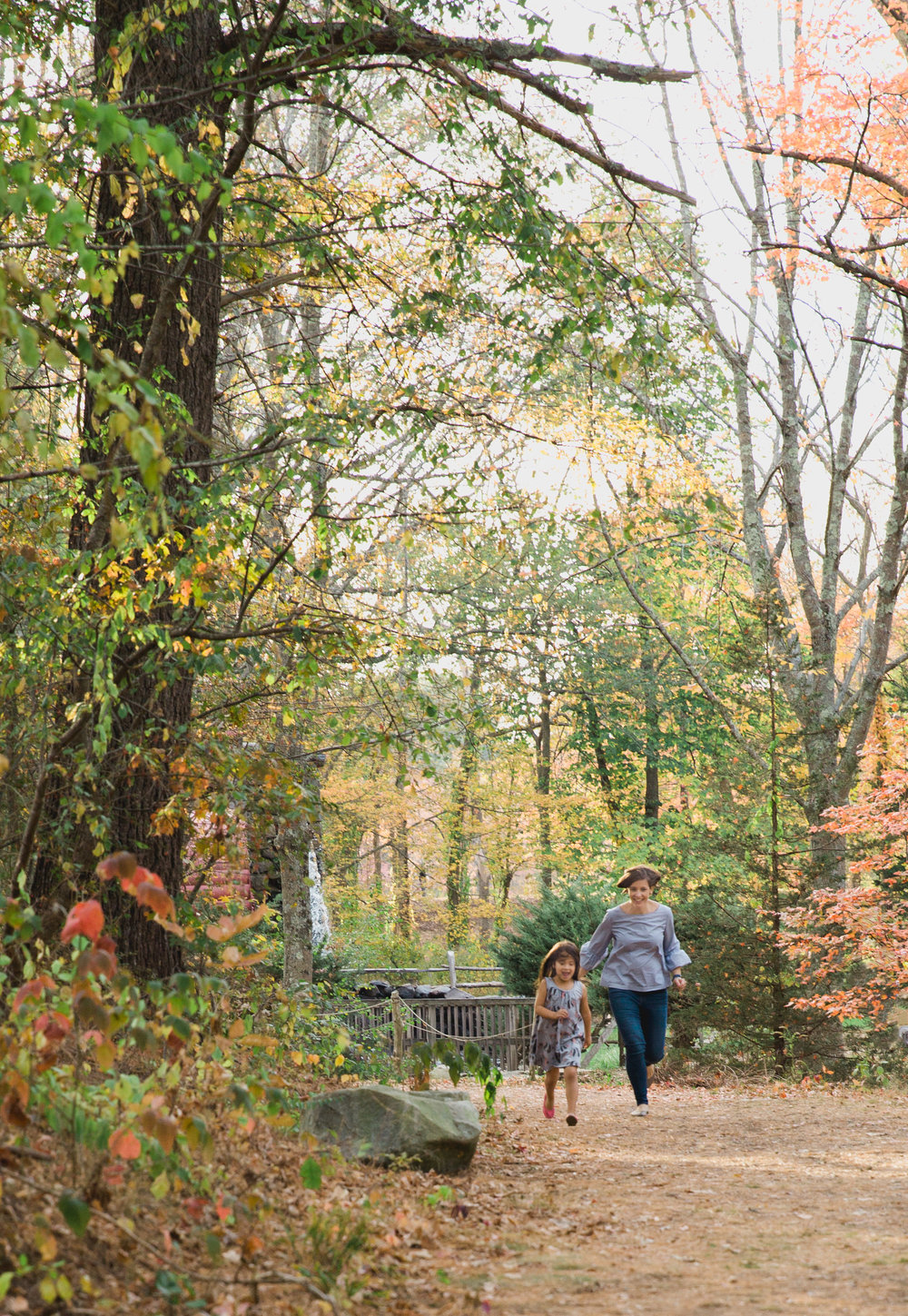 Greater Boston family photographer Joy Uyeno Sudbury mother and young daughter running under the fall foliage
