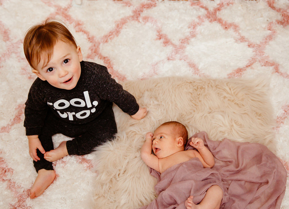 Toddler with newborn sister in Sudbury, Massachusetts at family photo session