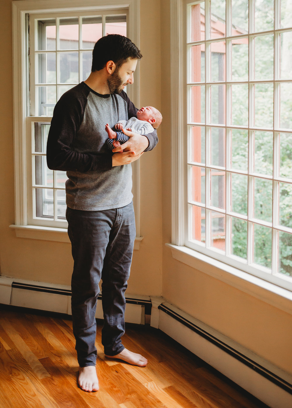Dad holding newborn near windows. Sudbury newborn photography / Boston family photographer / natural light / lifestyle