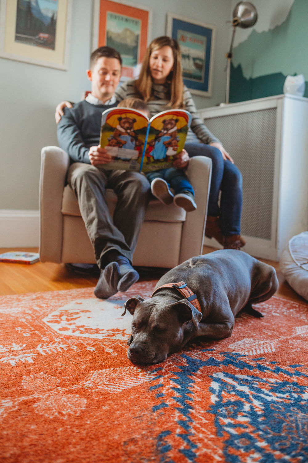 Parents sitting on rocker with toddler in Melrose, MA. Sweet grey pitbull sleeping on the rug at their feet. Boston family photographer.