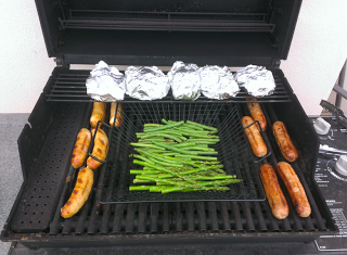 grilling sausage, potatoes, and fresh vegetables