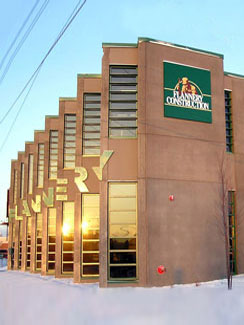 Flannery Construction - Flannery Construction incorporated solar thermal space heating and domestic hot water into their new facility to match up with their goals and to apply for LEED certification. The building itself was designed with energy efficiency strategies, and provides a mix of office spaces, conference room, and a workshop in the garage area. The solar thermal array is mounted on the rooftop and one of the most visible systems in the Twin Cities as it sits just off of I-94 by Snelling Avenue. Currently this is the largest solar thermal installation in Minnesota. The collectors were flown in by crane as three separate arrays, preassembled in the factory by Solar Mining Co. This reduced some of the labor costs for connecting individual panels.
