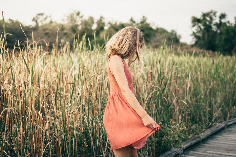 Senior girl dancing by tall grass
