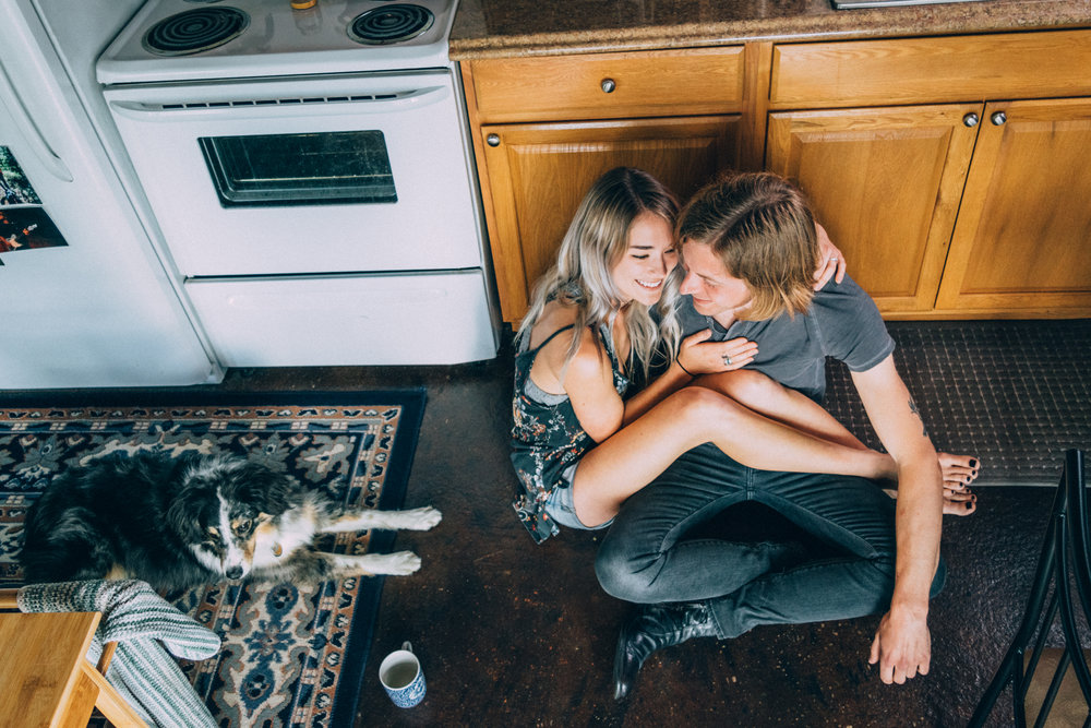 Two lovers laying on kitchen floor laughing