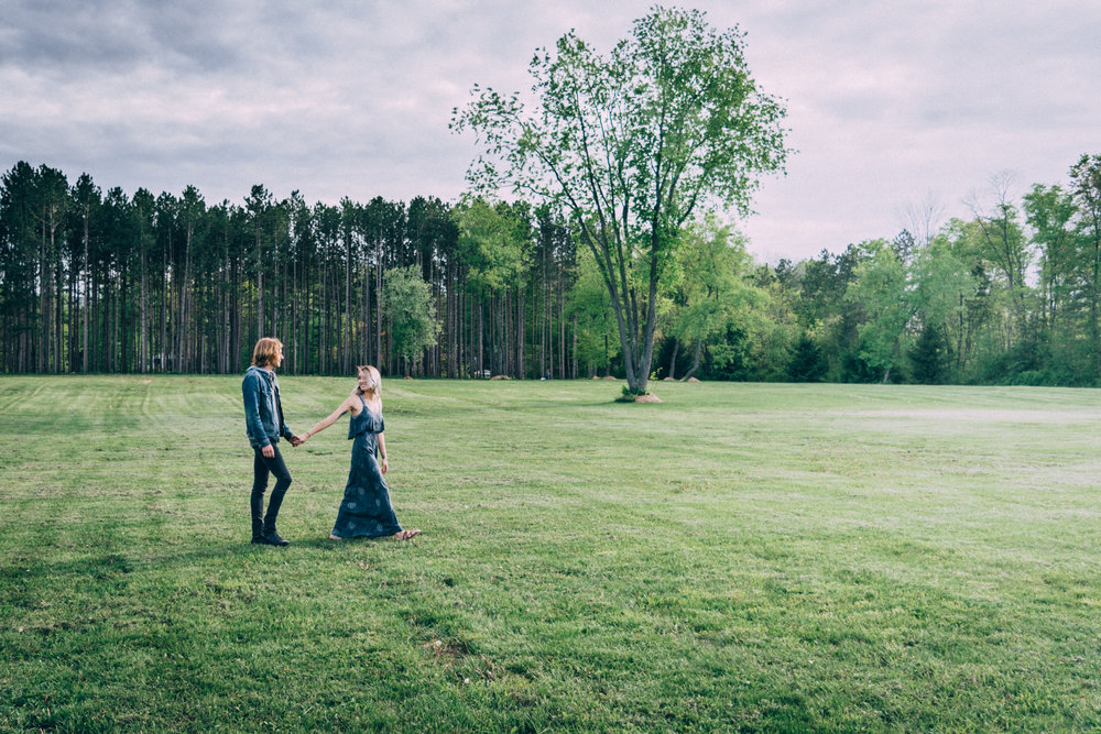 Engaged couple walking through field holding hands